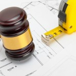 Wooden Judge Gavel With Measure Tape Above Construction Blueprint - Studio Shoot